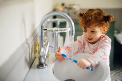 girl at sink with toothbrush