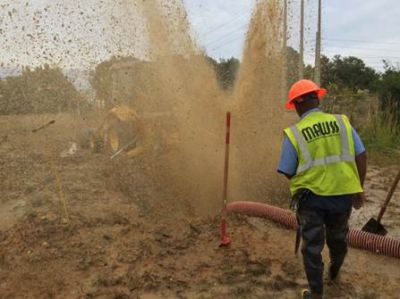 construction worker in front of spewing water pipe